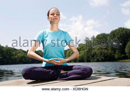 A young woman practicing yoga on a jetty - Stock Photo