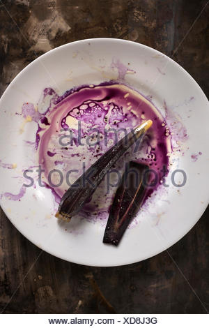 Purple carrot on a white plate with purple juices and oil creating a messy mixture all on a rustic metal surface. - Stock Photo