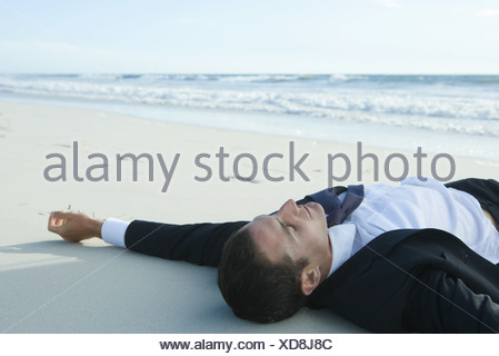 Businessman lying on sand, at beach - Stock Photo