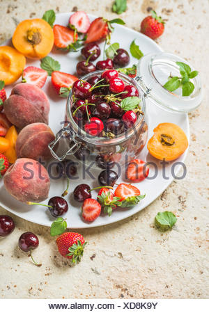 Healthy summer friut variety. Sweet cherries, peaches, strawberries on white serving plate over light concrete background. Top v - Stock Photo