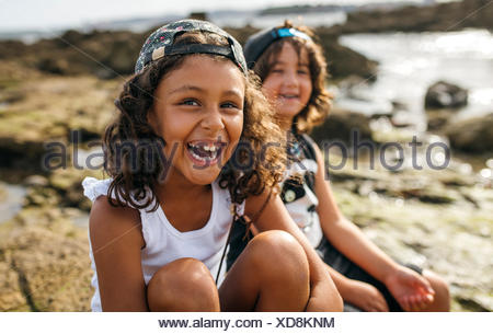 Spain, Gijon, portrait of laughing little girl and her friend in the background sitting at rocky coast - Stock Photo