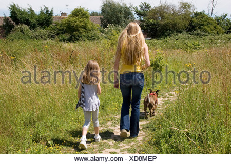 mother and daughter out with their staffordshire bull terrier dog - Stock Photo