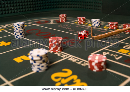 Dice and gambling chips on craps table - Stock Photo