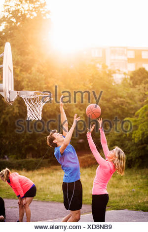 Man and woman playing basketball at park during sunset - Stock Photo