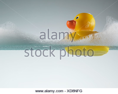 Rubber duck floating in soapy water - Stock Photo