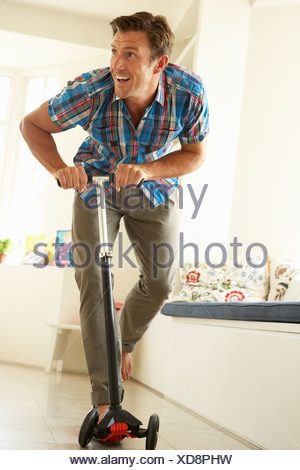 Man Riding Child's Scooter Indoors - Stock Photo