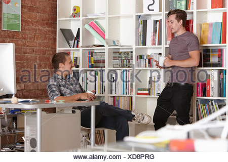 Two male colleagues chatting in office - Stock Photo