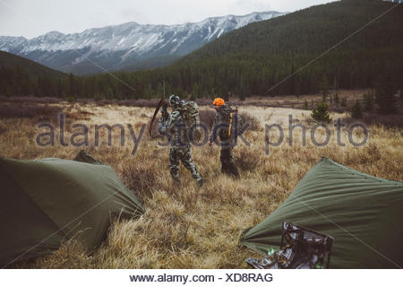 Male hunter friends walking outside tents at campsite in remote field below mountains - Stock Photo