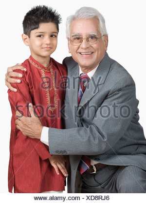 Portrait of a senior man hugging his grandson - Stock Photo