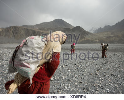 Women carry potatoes in sack, a two hour trek each way from the field. - Stock Photo