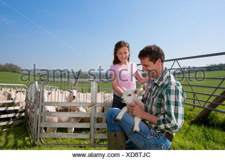 Shepherd and daughter holding lamb in pasture - Stock Photo