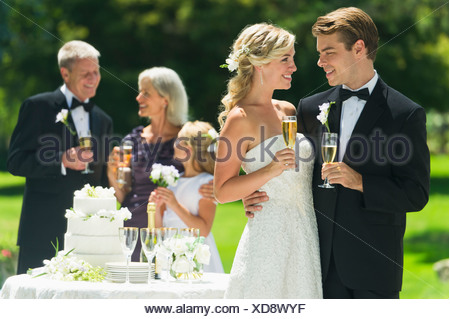 USA, New York State, Old Westbury, Married couple holding champagne flute, guests in background - Stock Photo