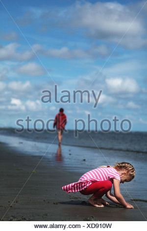 Girl (4-5) playing with sand with mother in the background at beach - Stock Photo