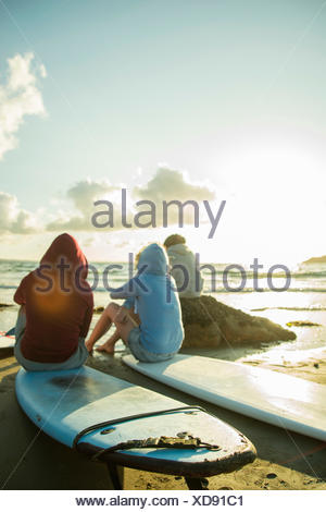 Three teenagers sitting on the beach watching sunset - Stock Photo