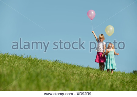 Germany, Bavaria, Girls standing in grass with balloons - Stock Photo