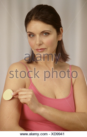 Female brunette hair wearing subtle make up and pink vest top sticking nicotine patch on upper arm looking to camera half - Stock Photo