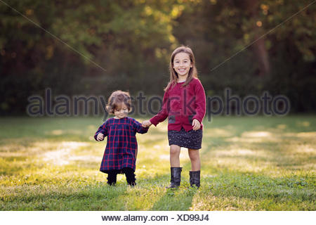 Two little girls walking hand in hand on a meadow - Stock Photo