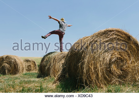Back view of a man balancing on one leg on top of a hay bale. - Stock Photo
