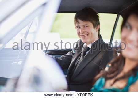 Teenagers driving car in formal wear - Stock Photo