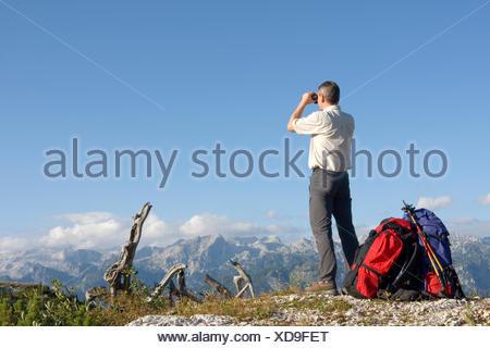 hiker with binoculars on mountaintop - Stock Photo