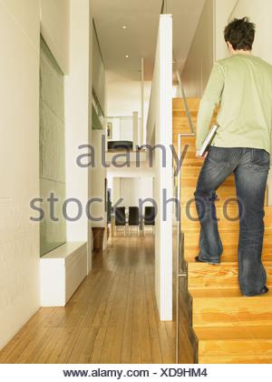 Man walking upstairs with laptop - Stock Photo