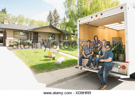 Portrait of couples at back of moving van - Stock Photo