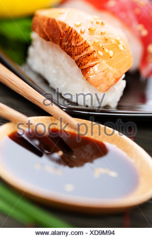 set of japanese sushi with chopsticks and soy sause over white - Stock Photo