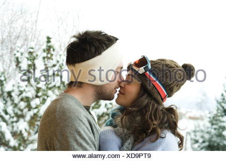 Young couple in winter clothes, kissing, side view - Stock Photo