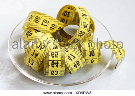 Yellow tapeline on glass bowl - Stock Photo