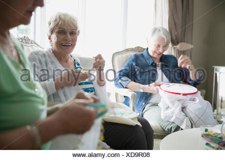 Portrait smiling senior woman embroidering with friends - Stock Photo