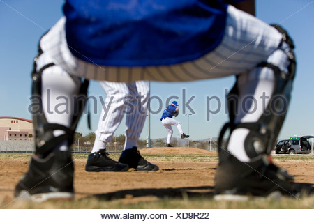 Baseball batter facing pitcher during competitive game, view through catcher's legs, rear view, focus on background - Stock Photo