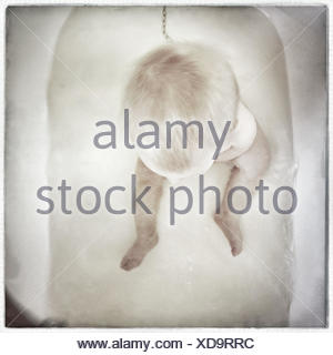 Overhead view of Baby sitting in bath - Stock Photo