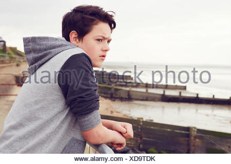 Unhappy teenage boy looking out from railings, Southend on Sea, Essex, UK - Stock Photo