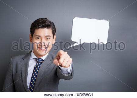 Portrait of young smiling businessman with a speech balloon pointing to front staring at front - Stock Photo