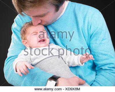 man comforting screaming baby - Stock Photo