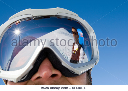 Snowboarder Troy Heithecker is reflected in skier Will Wacker's ski goggles on sunny day in the Canadian backcountry, Yukon Terr - Stock Photo