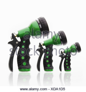 3 garden hose triggers nozzles in ascending size - Stock Photo