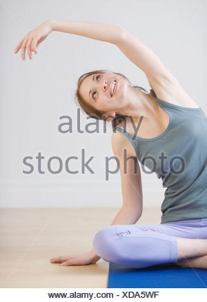 Woman stretching on yoga mat - Stock Photo