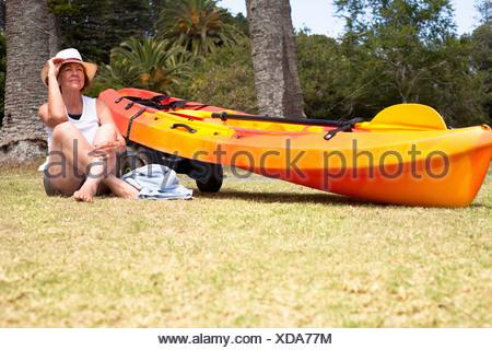 Senior woman sitting cross legged on beach - Stock Photo