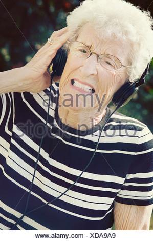 Sherwood Park, Alberta, Canada; A Senior Woman Cringing At The Music Coming Through Her Headphones - Stock Photo