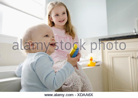 young girl with younger brother in bathroom - Stock Photo