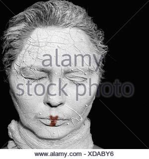 Close-Up Woman With Clay Covered Face Against Black Background - Stock Photo