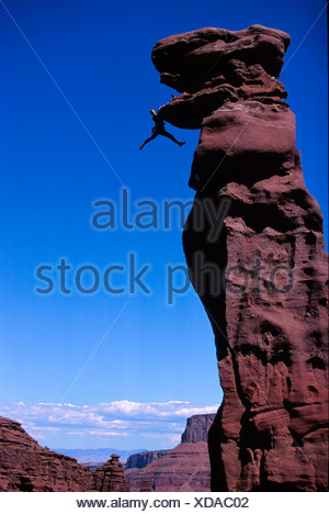 Rock climber in difficulty on overhang in Fisher Towers, Colorado River Waterway near Castle Valley in Moab, Utah, USA - Stock Photo