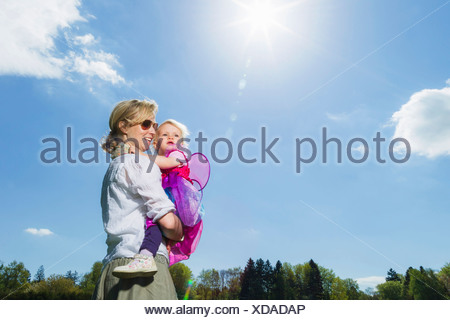 Mother carrying toddler girl outdoors - Stock Photo
