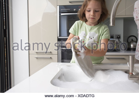 Girl washing dishes in kitchen - Stock Photo