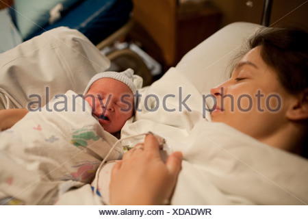 Mother holding newborn baby boy in hospital bed - Stock Photo