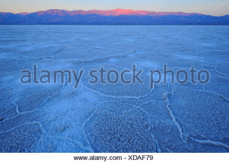 Salt pan, salt crystals, sunrise in Badwater Basin above Panamint Range, Death Valley National Park, Mojave Desert, California - Stock Photo