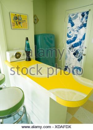 Lava lamp on lemon patterned worktop in fifties style kitchen with blue patterned roller blind on glass door - Stock Photo