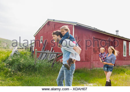 Parents carrying children outside - Stock Photo