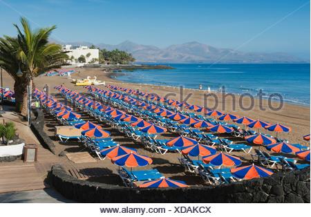 Beach umbrellas on the sandy beach, Playa Grande, Puerto del Carmen, Lanzarote, Canary Islands, Spain, Europe - Stock Photo